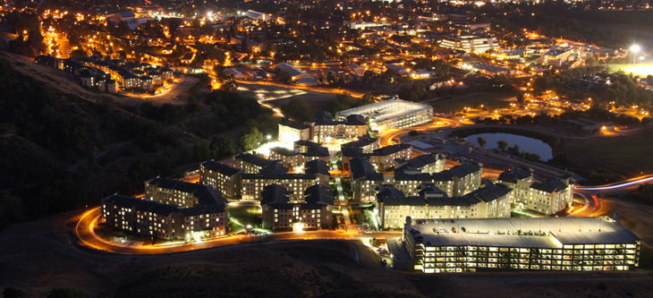 Aerial view of Cal Poly lit up at night, looking from over Poly Canyon